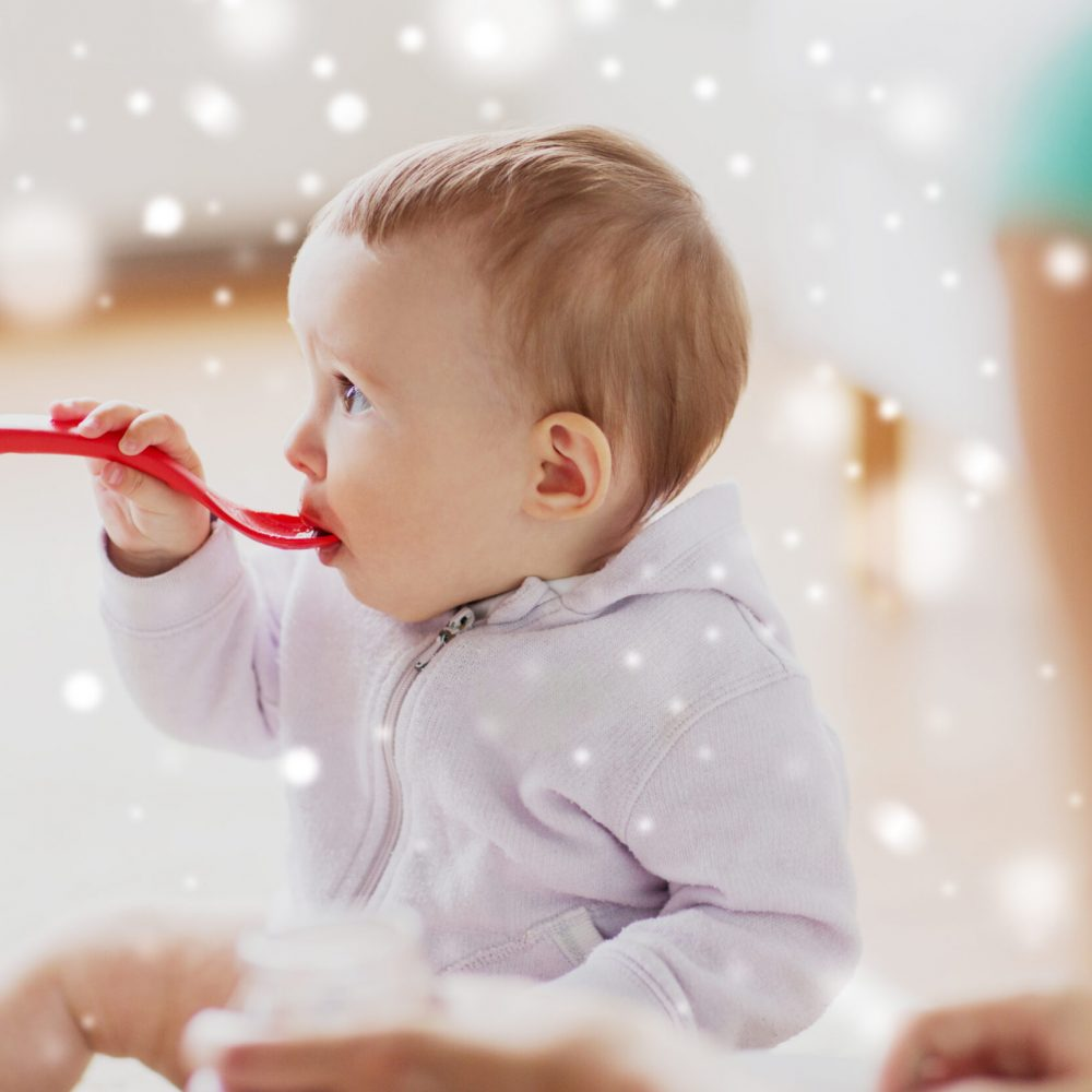 food, child, feeding and childhood concept - mother and baby with spoon eating at home over snow
